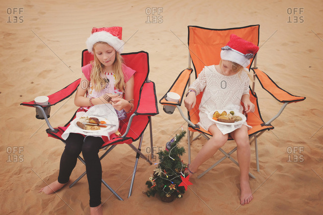 Girls eating Christmas meal in desert