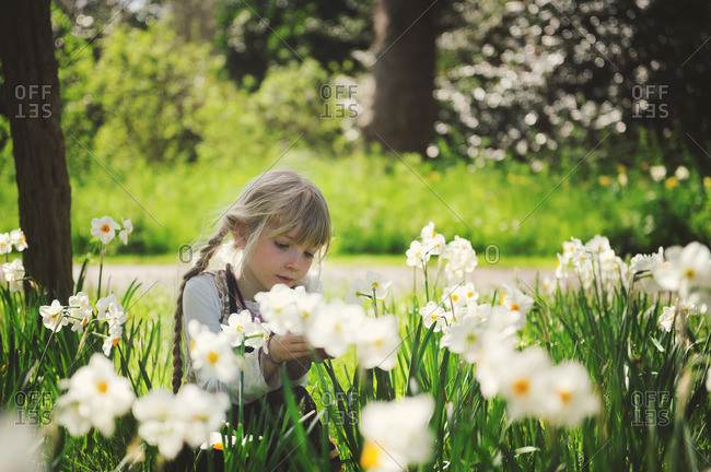 Girl sits among daffodils in spring