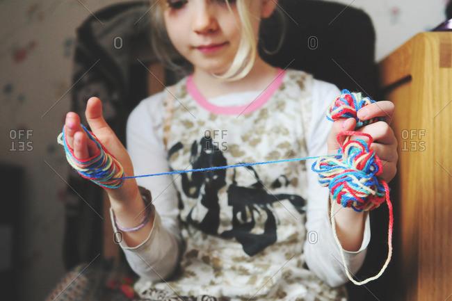 Girl winding yarn around her hands
