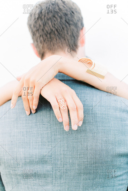 Bride's hand around groom's neck