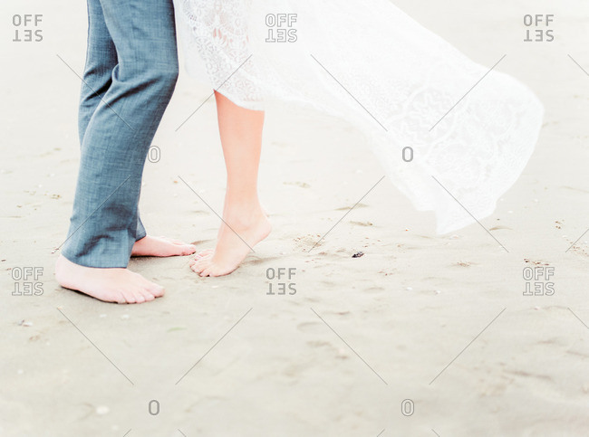 Barefoot bride and groom on beach