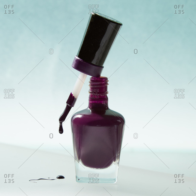Nail polish dripping from applicator brush on top of bottle stock ...