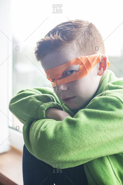 A 10 year old boy dressed as a superhero in an orange mask
