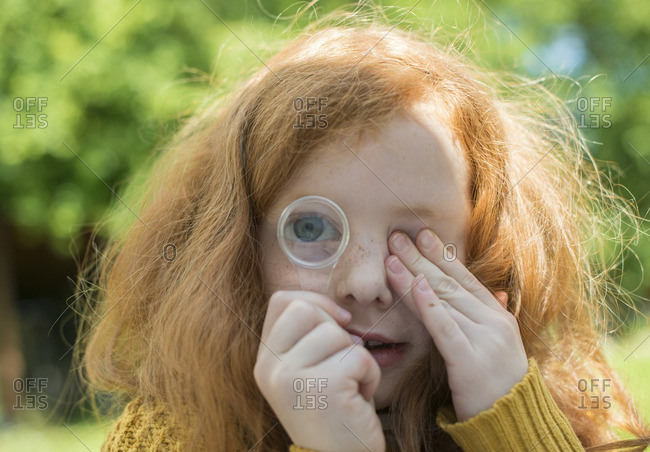 A little girl looking through a magnifying glass in her garden