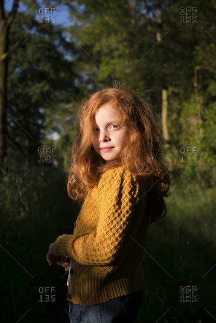 Portrait of an 8 year old girl with ginger hair standing in the sun in the woods