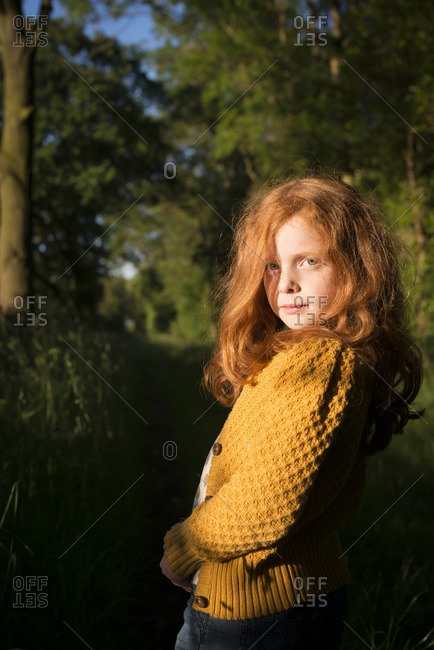 Portrait of an 8 year old girl with red hair standing in the sun in the woods