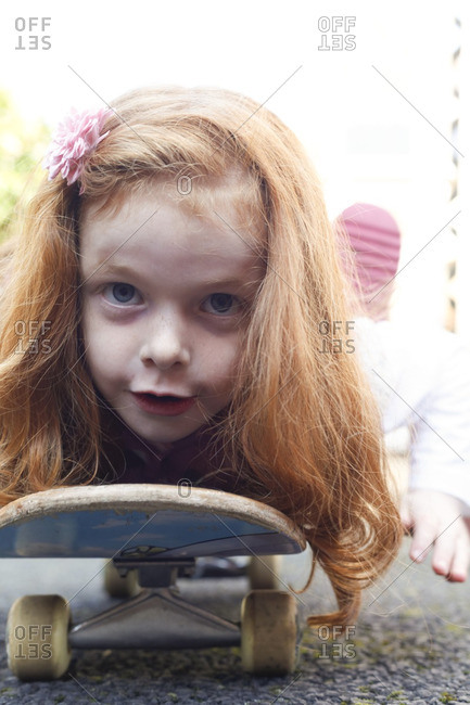 6 year old girl with red hair lying down on a skateboard