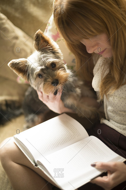 Woman reading a book on a sofa with her dog