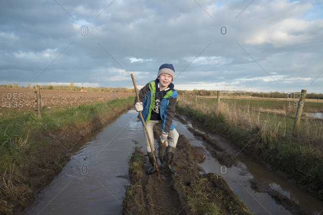 A boy walking along a muddy road in the English countryside