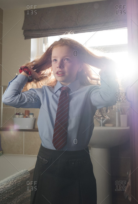 Young girl getting ready for school in the bathroom