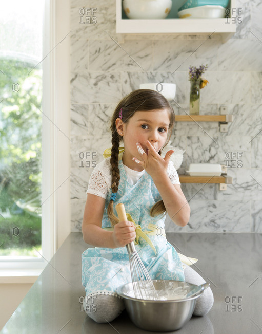 Girl sitting on kitchen counter tasting whipped cream from a bowl