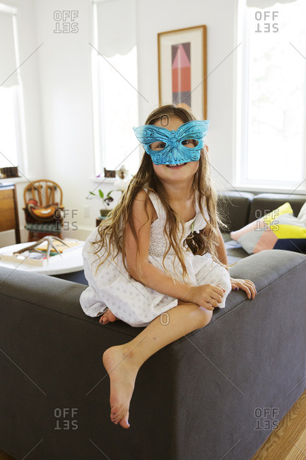 Girl wearing white dress and blue butterfly mask on back of a couch