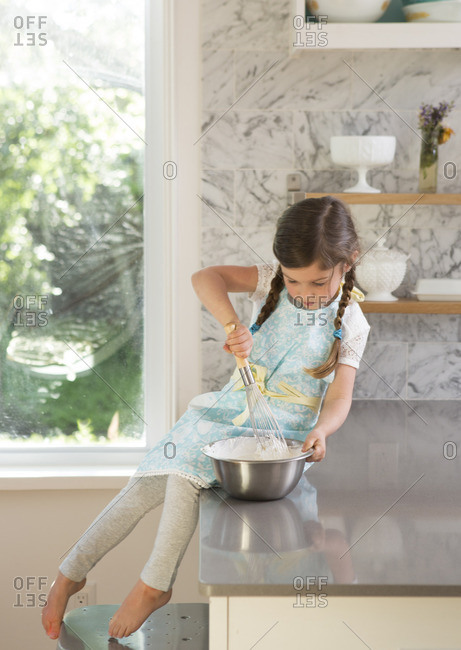 Young girl sitting on the kitchen counter stirring whipped cream