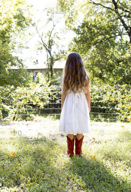 Girl in a field of grass wearing white dress and red cowboy boots