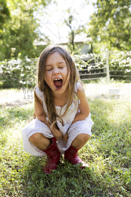 Young girl in red cowboy boots screaming with her eyes closed