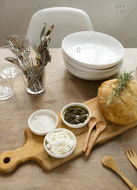 Bread and cutting board with bowls and serving pieces for entertaining