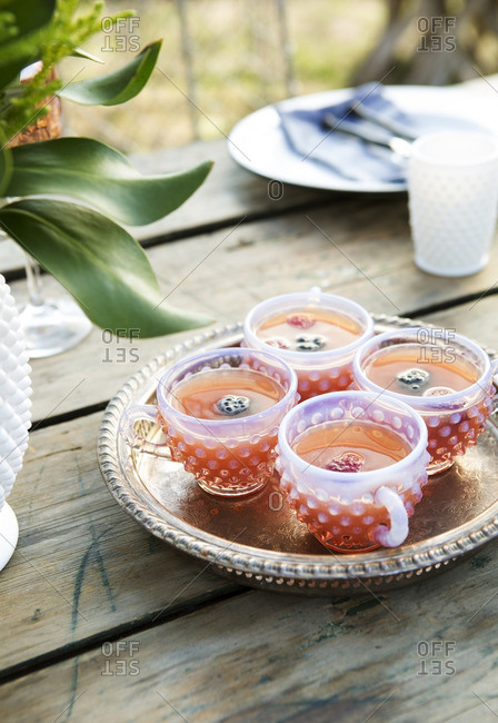 Vintage hobnail cups with punch and fruit on an outdoor table