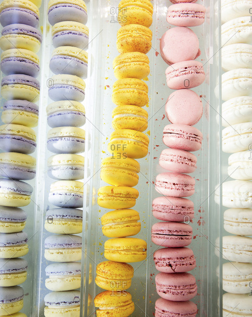 Rows of colorful macaroons in a bakery case
