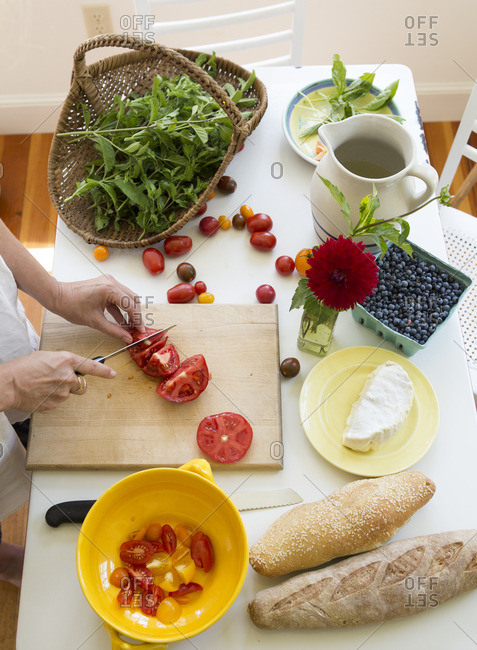 Woman slicing tomatoes on a table with fresh basil, blueberries, cheese and bread