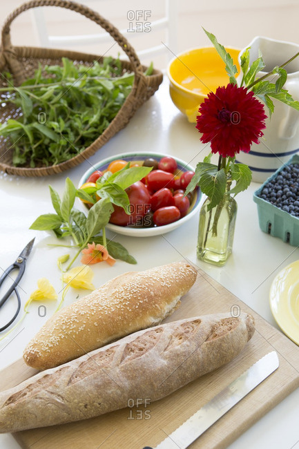 Table with fresh tomatoes, blueberries, basil and bread