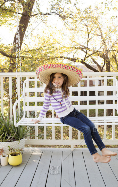 Girl on front porch on a swing wearing a sombrero
