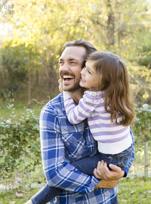 Father and daughter hug outside while laughing