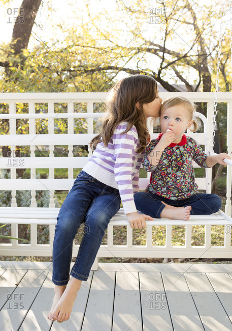 Girl kissing her little sister on a porch swing
