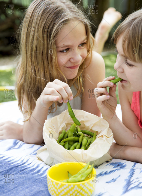 Girls on a blanket outside sharing edamame