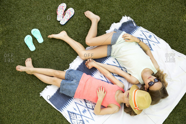 Girls relaxing on a blanket outdoors