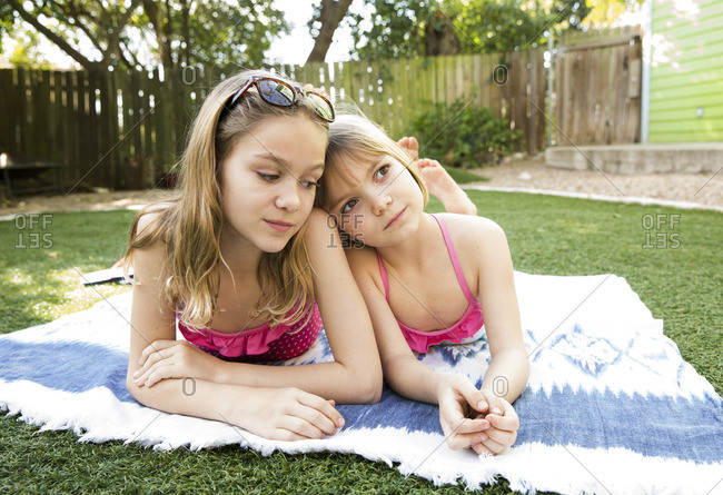 Sisters relaxing on a blanket in their bathing suits outdoors