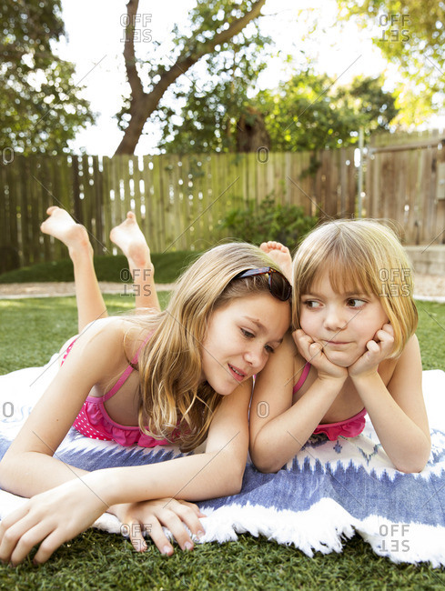 Two sisters laying on a blanket in the backyard together