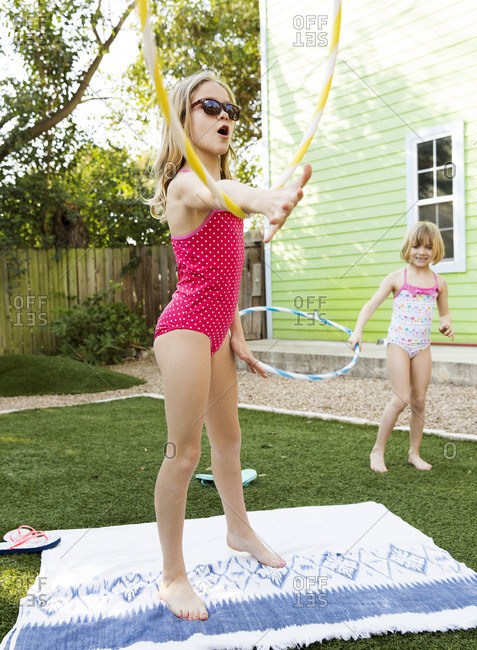 Two girls playing with hula hoops in their backyard