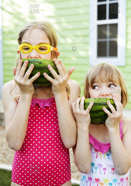 Two sisters eating watermelon together