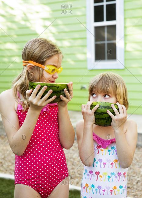 Sisters eating watermelon in their backyard