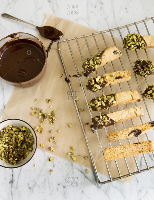 Chocolate dipped biscotti cookies with pistachios being prepared