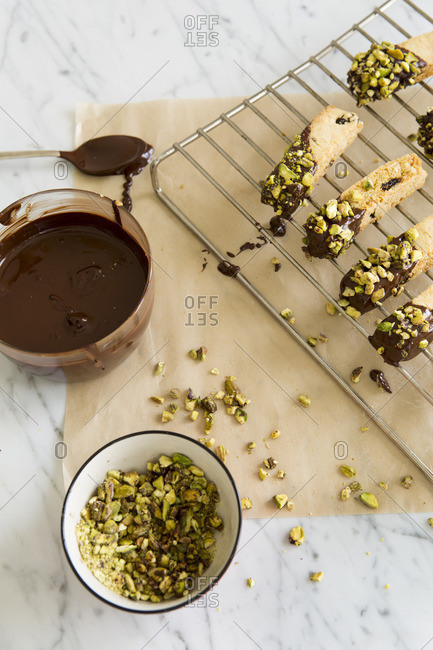 Chocolate dipped biscotti biscuits with pistachios being prepared