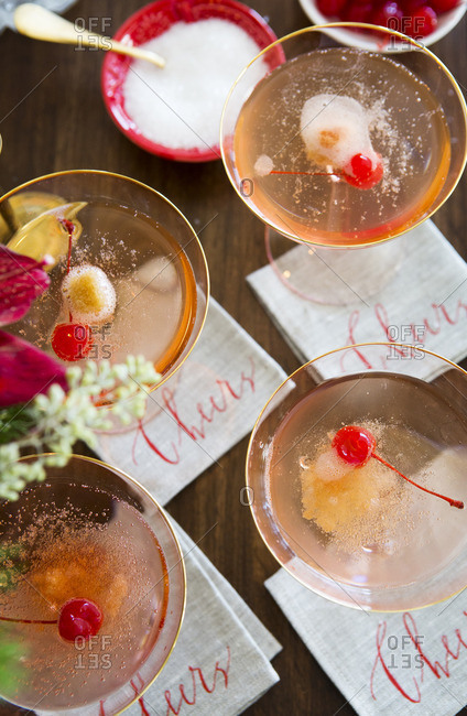 Champagne cocktail on a bar with sugar cube and maraschino cherry