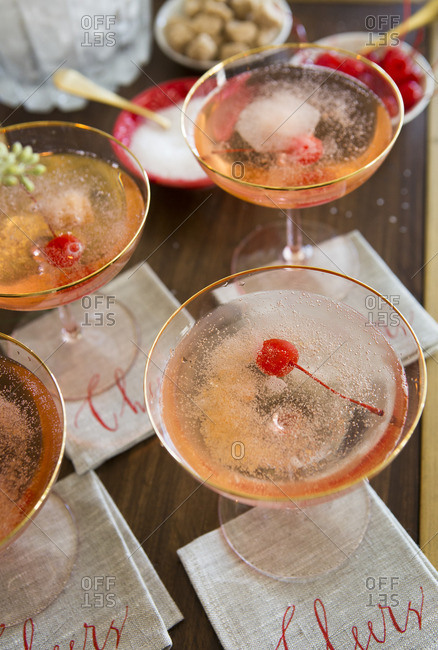 Champagne cocktail served with sugar cube and maraschino cherry