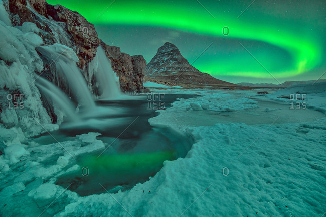Northern lights over Kirkjufell mountain with water falls during winter, Iceland