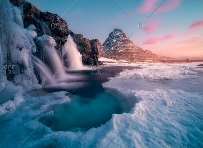Kirkjufell mountain with icy waterfalls in the winter at sunrise, Iceland