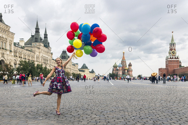 Moscow, Russia - July 22, 2016: A young girl with colorful balloons posing for a photo in the Red Square in Moscow