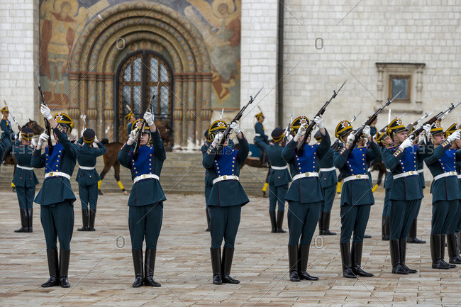 Moscow, Russia - July 23, 2016: Guards raising their guns during a ceremony at the entrance of the Dormition Cathedral in Cathedral Square in the Moscow Kremlin