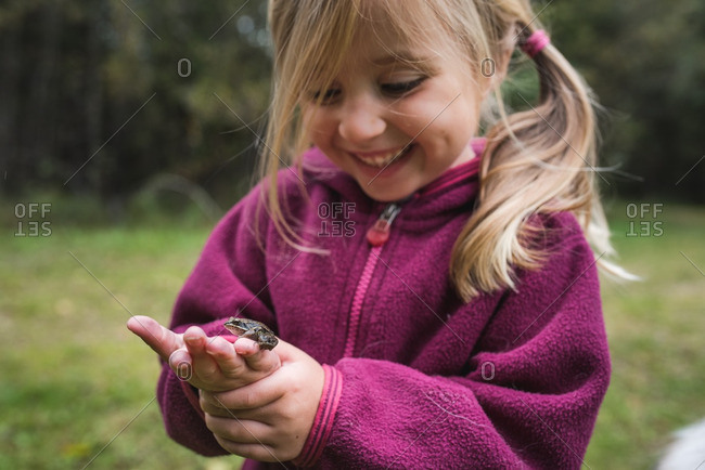 Little girl holding a frog she's caught in the palm of her hand