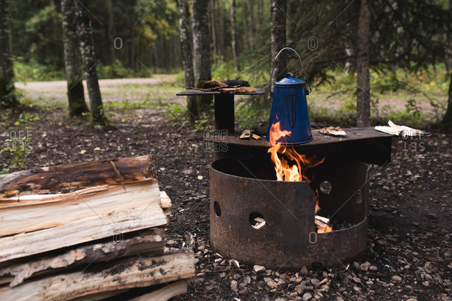 Kettle heating up on a fire pit at a campground