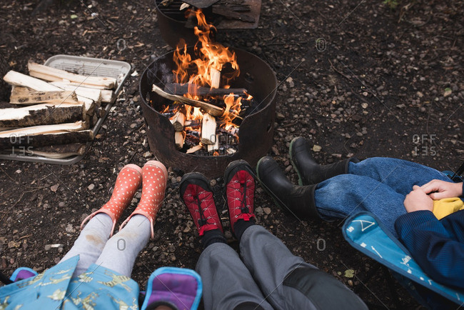 Feet of a family in rubber boots beside a campfire