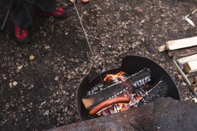 Man roasting a hot dog over a fire pit at a campsite