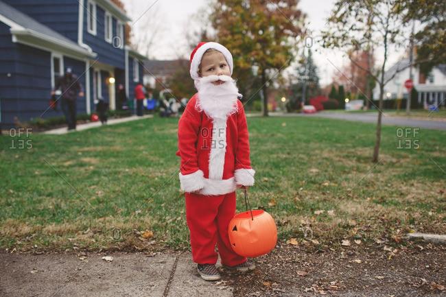 Sad child dressed as Santa Claus on Halloween