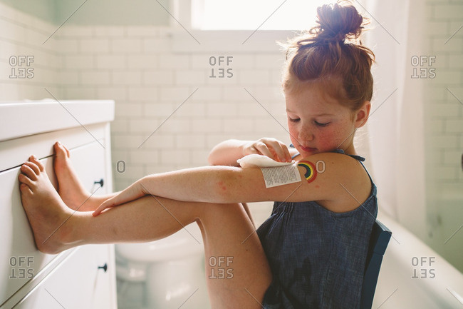 Girl applying a temporary tattoo to her arm in bathroom