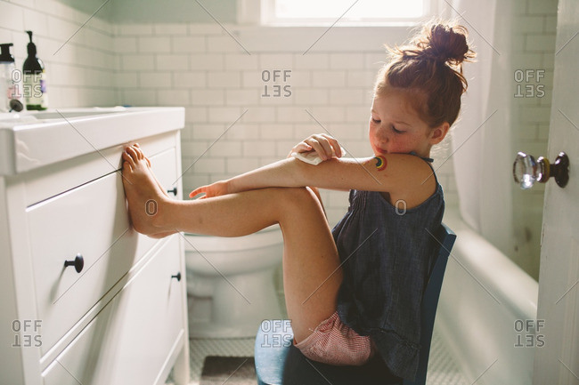 Girl putting on a temporary tattoo in the bathroom. girls bathroom stock photos   OFFSET