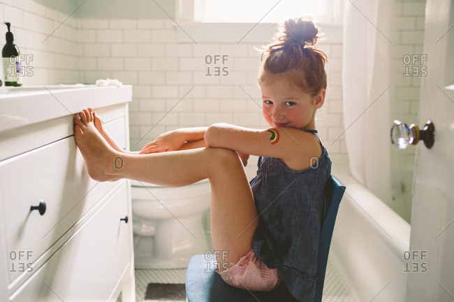 Portrait of a young girl with temporary rainbow tattoo in bathroom